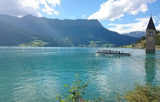 1280px-reschensee_with_graun_church_tower_and_boat